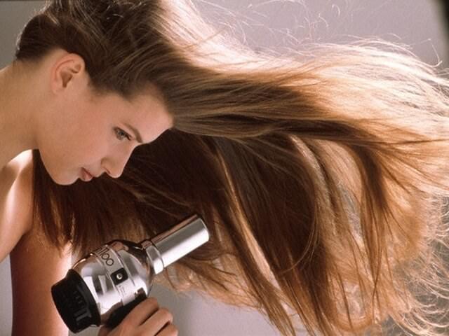 Длинноволосая девушка сушит волосы феном