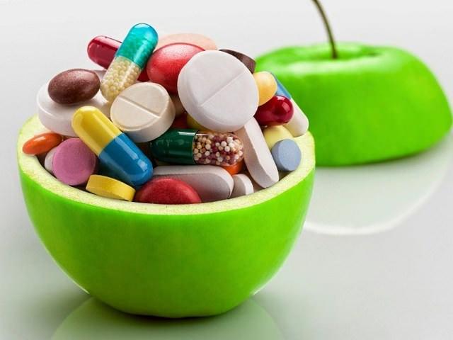 Витамины разных видов в чаше в виде яблока