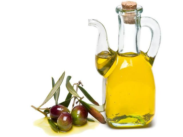 Оливковое масло и оливки на белом фоне