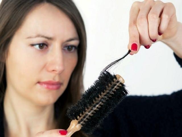 Девушка с выпавшими волосами на расческе
