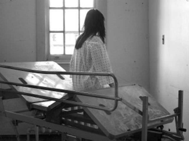 Девушка, сидящая на кровати в психбольнице