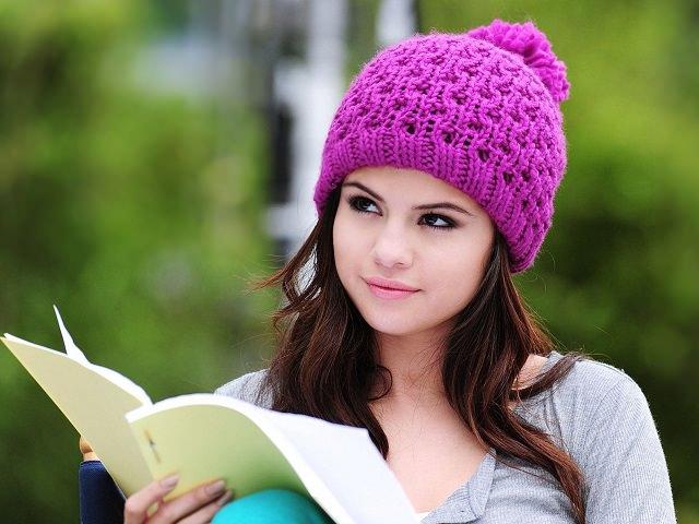 Девушка в шапке читает книгу
