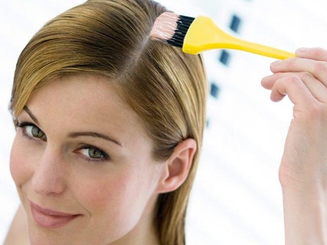 Девушка наносит маску против выпадения волос кисточкой