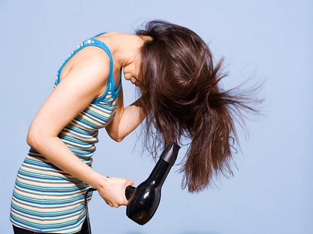 Девушка сушит волосы феном, наклонившись вперед