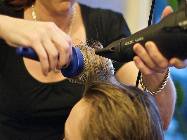 Девушке укладывают волосы феном