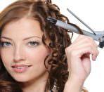 Девушка укладывает волосы средней длины плойкой