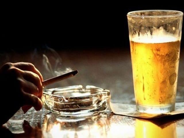 Курение и алкогольный напиток в стакане