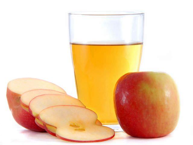 Яблоки и уксус из яблок в стеклянном стакане