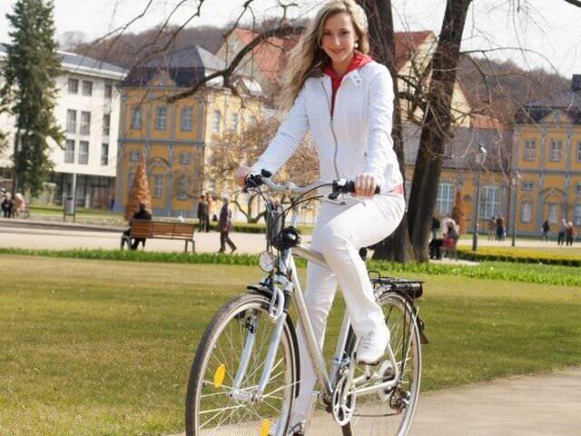 Длинноволосая девушка в белой одежде едет на велосипеде
