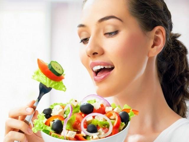 Девушка с темными волосами держит в одной руке тарелку с овощным салатом, а в другой - вилку