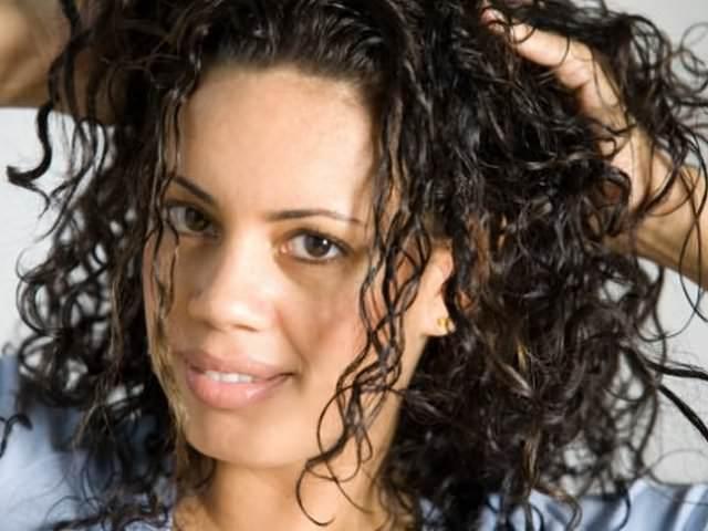Вьющиеся волосы девушки, уложенные с помощью удерживающих и фиксирующих средств
