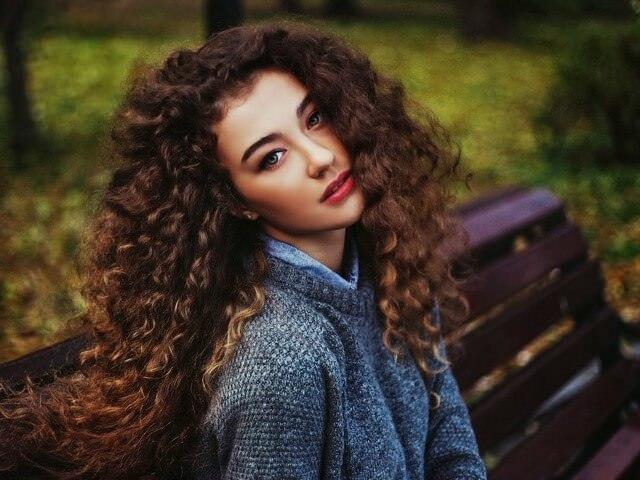 Девушка с длинными вьющимися волосами в парке на скамейке