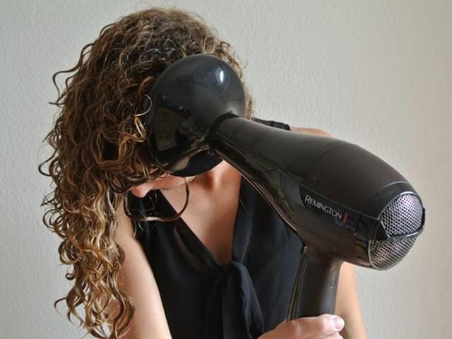 Девушка с длинными вьющимися волосами сушит кудри при помощи диффузера