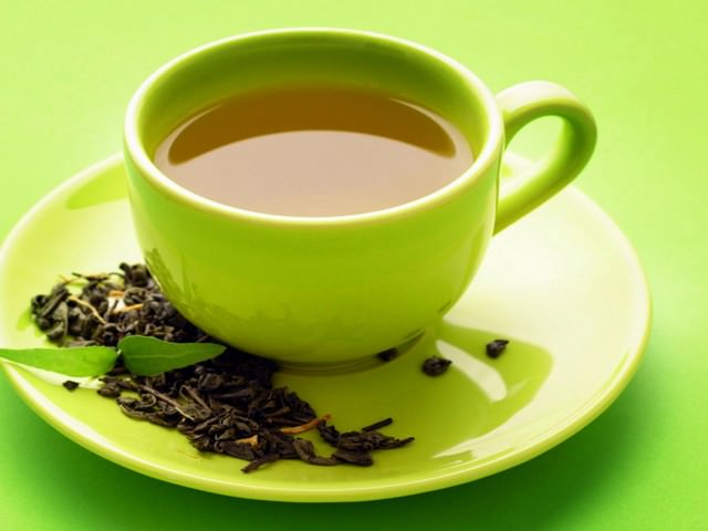 Чашка зеленого чай на зеленом фоне